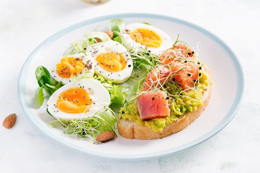 breakfast-healthy-open-sandwich-on-toast-with-avocado-and-salmon-boiled-eggs-herbs-chia-seeds-on-white-plate-with-copy-space-healthy-protein-food
