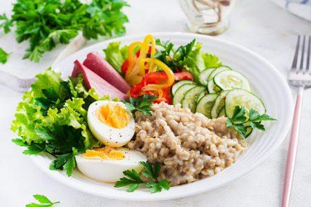 Breakfast oatmeal porridge with boiled egg, ham and vegetables salad. Healthy food.