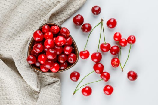 Cherries in a bowl flat lay on white and kitchen towel background