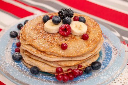 Delicious oats and banana pancakes with mixed berries fruits and sugar powder.