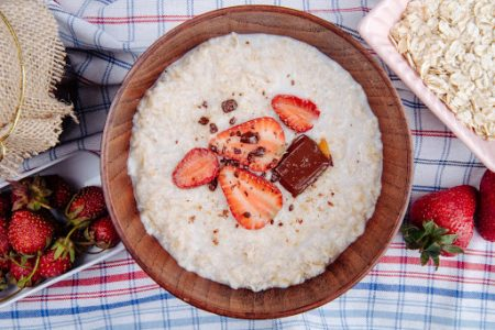 top view of oatmeal porridge with fresh strawberries and chocolate in a wooden bowl on plaid fabric
